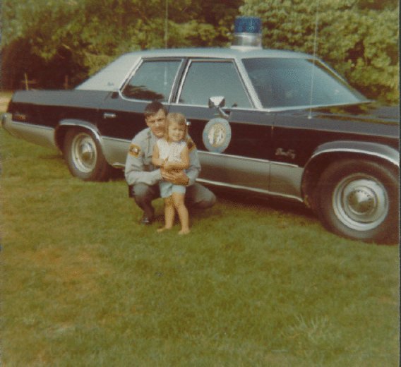 Stephanie Greer with her father Dallas Pate in front of his patrol car